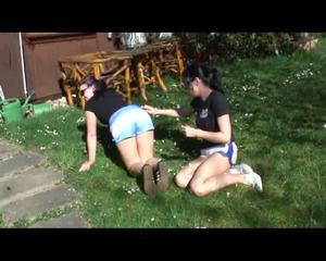 Jill and a friend of her lolling and touching in the garden on the floor wearing shiny nylon shorts (Video)