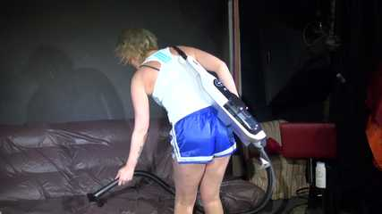 Watching sexy Pia wearing a sexy blue/white oldschool shiny nylon shorts and a muscle shirt assembling a vaccum cleaner and cleaning with it the sofa (Video)