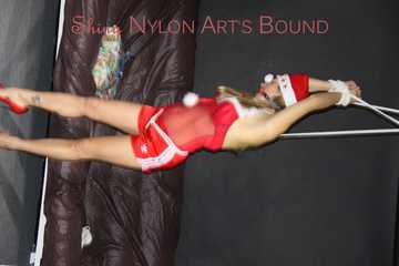 Watching Sandra wearing a sexy santaclause shiny nylon outfit with shiny nylon shorts being tied and gagged overhead with ropes and a ballgag (Pics)