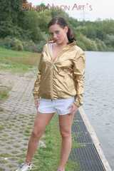 Watching out beautiful archive girl wearing a white shiny nylon shorts and a golden rain jacket posing outdoor (Pics)