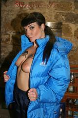 Jill posing in a cooling room wearing a shiny nylon rainpants and a down jacket (Pics)