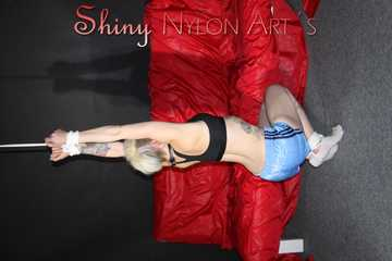 Watching ***NEW MODELL COURTNEY*** wearing a sexy lightblue shiny nylon shorts and a black top being tied and gagged overhead with ropes and a ballgag (Pics)