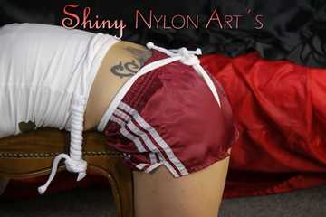 Watching sexy Sandra being tied and gagged with ropes and a clothgag on a stool wearing a sexy darkred shiny nylon shorts and a white top (Pics)