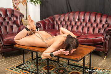 Elegant Leah in chains wriggling on the table - photos