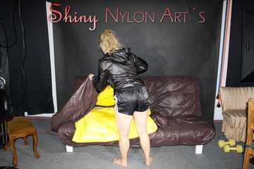 Watching Sophie wearing a sexy black shiny nylon shorts and a black shiny nylon rain jacket preparing her bed and lolling in the shiny cloths (Pics)