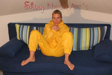 Sexy blonde archive girl posing and lolling on a sofa wearing sexy yellow rainwear over nothing (Pics)