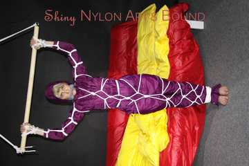 Watching sexy Sonja wearing a supersexy purple shiny nylon rainwear combination being tied and gagged overhead with ropes and a clothgag (Pics)