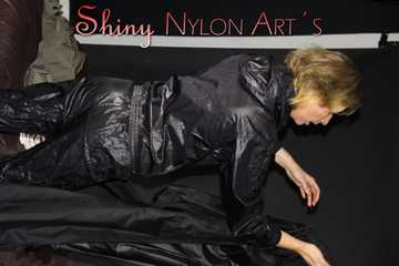 Watching Pia wearing a sexy black shiny nylon suit and a shiny nylon rain coat posing and changing clothes (Pics)