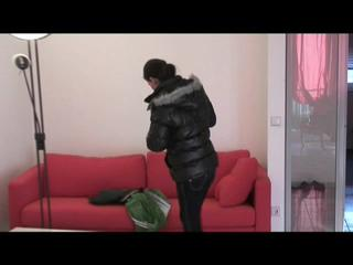 Enni with black shiny nylon shorts and rain pants and a rain jacket over naked skin smoking a cigarette (Video)